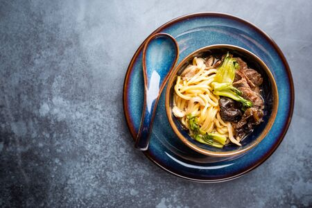 Asian ramen noodles soup with beef, oyster mushrooms and vegetables in bowl on gray background, top view Stock Photo