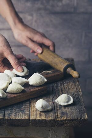 The process of making homemade dumplings. Raw homemade dumplings with meat on a wooden board with women hands Stock Photo