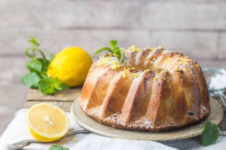 Homemade lemon bundt cake with icing sugar on a black background