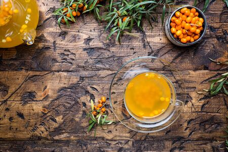 Tea with sea buckthorn on wooden background. top view
