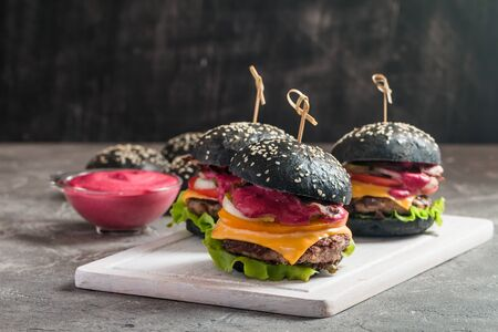 Gourmet black burger with berry sauce on wooden cutting board and dark background