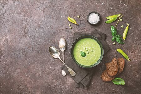 Green pea cream soup in black bowl over dark stone background, top view