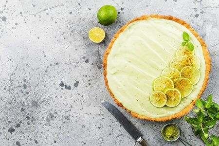 Key Lime Pie with several limes and mint over gray background, top view with copy space.