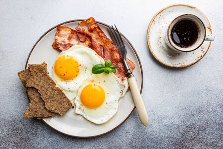 Fried eggs and bacon for breakfast on a plate, top view, copyspace