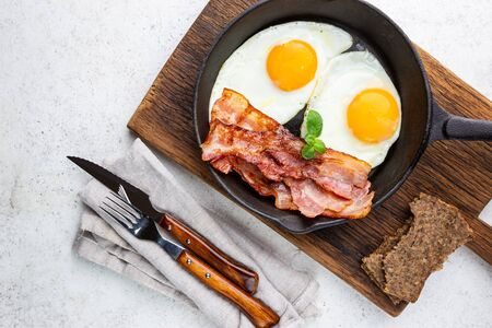 Fried eggs and bacon for breakfast on a frying pan, top view, copyspace