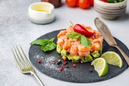 Delicious avocado and raw salmon salad, tartare, served on a black plate with lime, light background Imagens