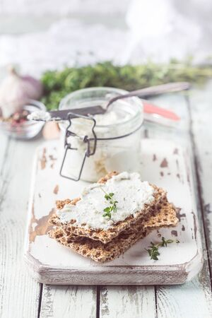 Crispbread toast with homemade herb and garlic cottage cheese on wooden background Stok Fotoğraf