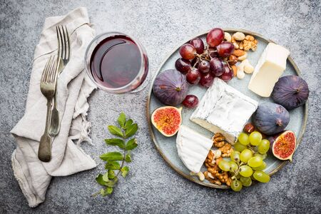 Camembert or brie cheese with fresh figs, honeycomb and glass of wine on plate over gray backdrop, top view, copy space Stok Fotoğraf
