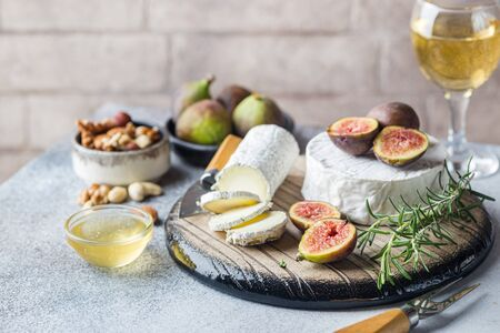 Fresh goat brie cheese with truffle and white mold on cheese platter with figs and honey