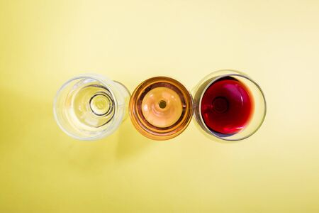 Glasses with white, red and pink wine on yellow background, top view