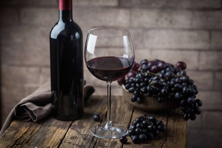 Red wine in a glass and ripe grapes on wooden table Reklamní fotografie