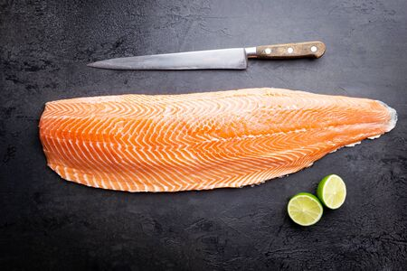 Fresh raw salmon or trout sea fish fillet on black background, top view