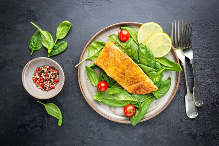 Grilled Spiced Salmon with fresh Spinach and Tomatoes Salad and Lemon Slices, top view Stock Photo