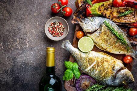 Pescado dorado al horno, besugo con verduras asadas, hierbas y condimentos, vista superior