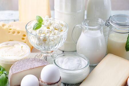 Verse zuivelproducten, melk, kwark, eieren, yoghurt, zure room en boter op houten tafel