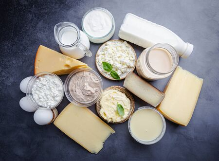 Fresh dairy products, milk, cottage cheese, eggs, yogurt, sour cream and butter on black background, top view