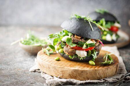 Veggie mushroom, green salad and vegetable black burgers. on gray stone background Copyspace. Stock Photo