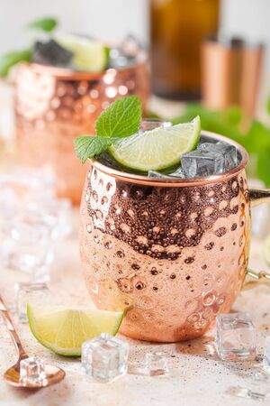 Cold Moscow Mules cocktail with ginger beer, vodka, lime. White stone background.