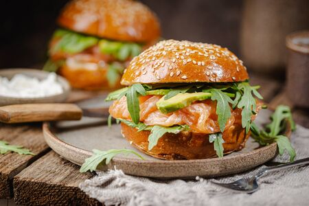 Burger sandwich with salmon, cream cheese, avocado and arugula on a light background, concept diet food, take away, healthy fast food