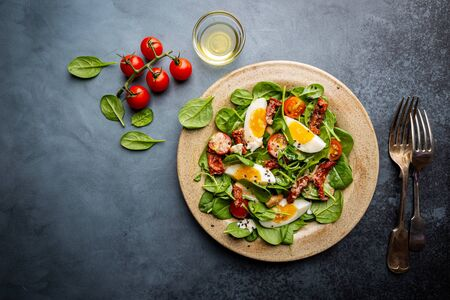 Salad with spinach, sun-dried tomatoes and eggs. Healthy home made food. Concept for a tasty and healthy meal. Top view. Copy space.