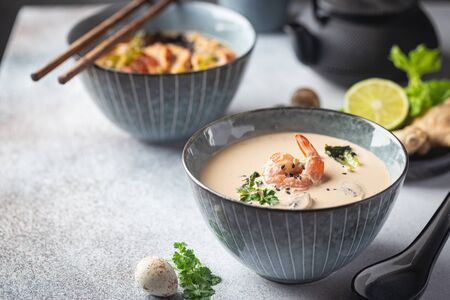 Tom Yum Kung soup, a Thai traditional spicy prawn soup in a bowl on gray background Imagens
