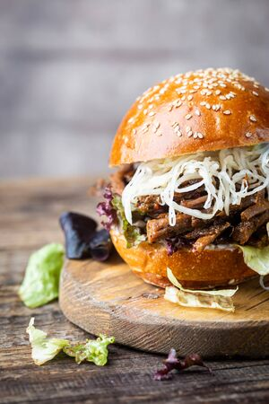 Pulled beef burger with cabbage salad and bbq sauce on cutting board