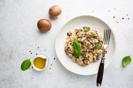 Risotto with mushrooms in a white plate over white background, top view