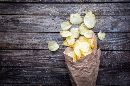 Opened paper pack of delicious spicy potato chips over dark wooden table, top view
