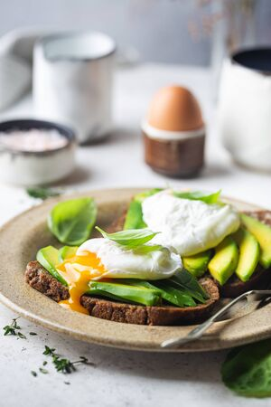 Healthy breakfast whole wheat toasted bread with avocado and poached egg over white background