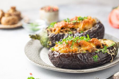 Baked aubergine or eggplant boats stuffed with mushrooms, vegetables and cheese