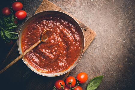 Classic homemade Italian tomato sauce with basil for pasta and pizza in the pan on a wooden chopping board on brown background, top view.
