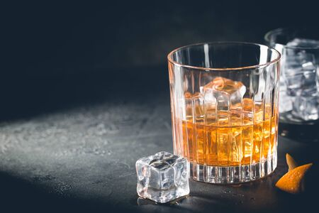 Glass of scotch whiskey with ice cubes on black background Standard-Bild