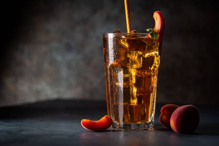 Glass of peach or apricot iced tea with fruit slices against dark blue background Foto de archivo