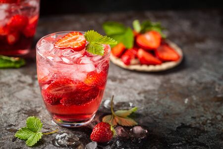 Refreshing summer drink with strawberry slices in glasses on dark background