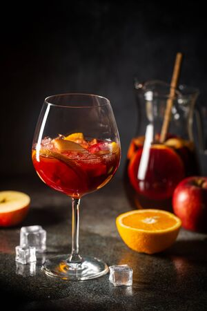 Refreshing red wine sangria or punch with fresh fruits in glasses and pincher on black background Zdjęcie Seryjne