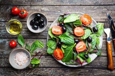 Healthy salad, leaves mix salad with mangold, spinach and vegetables in the plate over wooden background, top view. Food background.