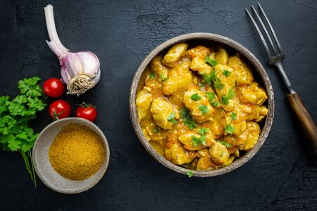 Spicy chicken cooked with curry sauce in a bawl, top view Stock Photo