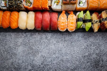 Set of sushi and maki with soy sauce over stone gray background. Top view with copy space