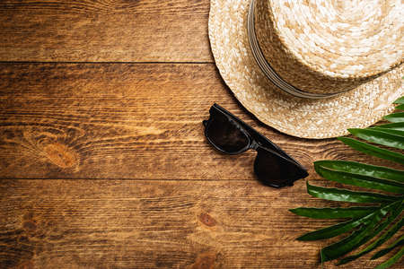 Straw beach hat and sun glasses top view on wooden background, summer flat lay