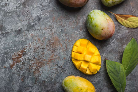 Fresh mango tropical fruits over gray background, top view with Copy space.