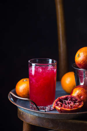 Glass of blood orange juice with ice and orange fruits on dark background Reklamní fotografie