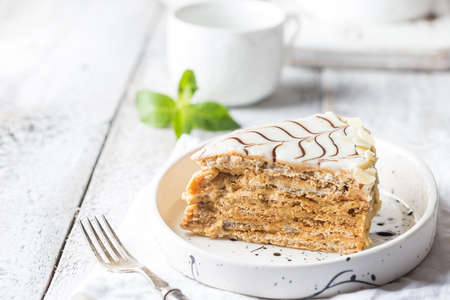 Traditional Hungarian Esterhazy piece of cake on a white wooden background.