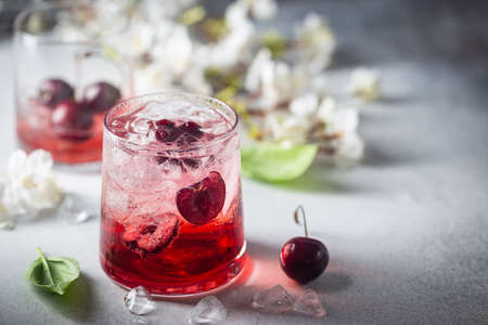 Cold cherry lemonade drink with fresh cherry and ice on gray background