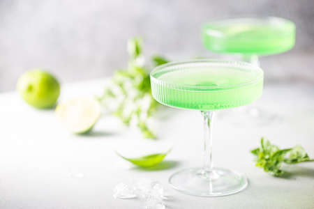 Summer green cocktail with lime, basil and ice in a crystal glass