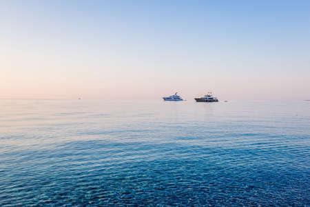 Luxury yacht on open sea at pink sunrise