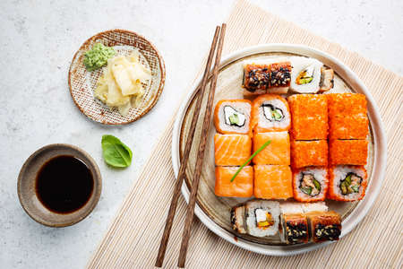 Set of sushi and maki with soy sauce over white background. Top view with copy space