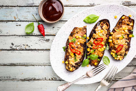 Baked aubergines boats, stuffed with minced meat, tomatoes, corn, garlic and cheese in white plate, top view