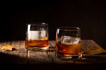 Glass of scotch whiskey and ice on wooden background 免版税图像