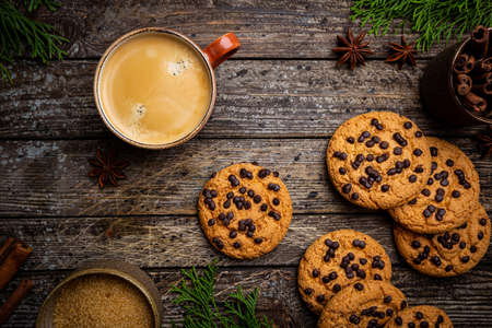 Homemade Chocolate chip cookies with coffee on rustic wooden table, top view