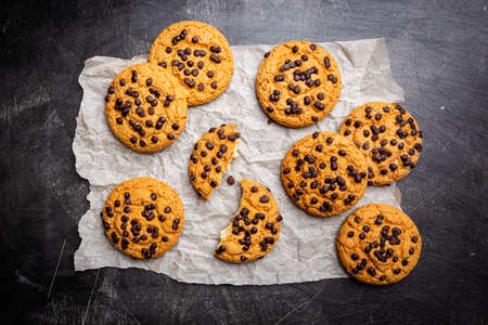 Homemade Chocolate chip cookies on paper over dark background, top view